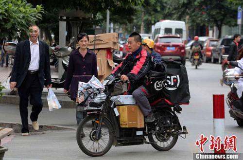 一名快递公司送货员正骑着满载快件的电单车在市区内送货。李俊锋摄