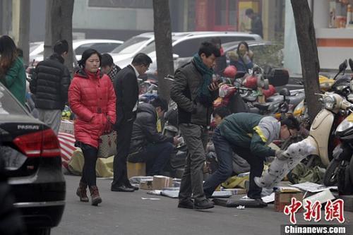 一家快递公司的员工蹲在马路边分发邮件,身边堆放着大量的包裹。王中举摄