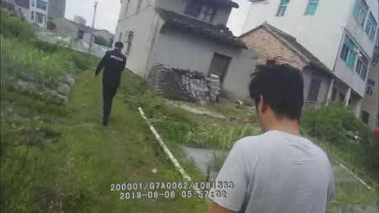 当天早上6时左右,男子(穿T恤者)被民警带回派出所做调查。