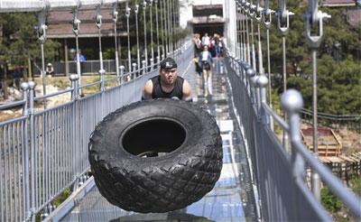 湖南平江举行高空玻璃桥中外大力士翻轮胎大赛