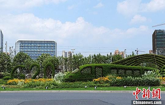 7月15日,浙江杭州最大交通樞紐杭州東站旁的綠色植物景觀將G20與高鐵元素相結合,成為一道亮麗的風景線。中新社記者 王剛 攝 作為2016年G20峰會的舉辦地,杭州城市面貌在不斷地美化。近段時間,杭州將G20與本地化元素相結合建造了新的綠植景觀,成為一道道亮麗的城市風景線。