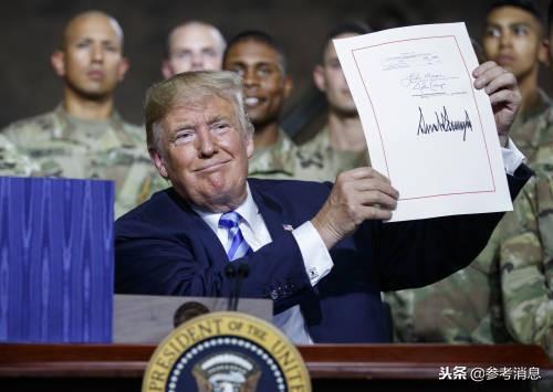8月13日,在美国纽约州一处军事基地,美国总统特朗普展现他在2019财年国防授权法案文本上的签名。(新华/美联)